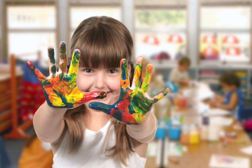 Happy Girl Painting With Her Hands in Kindergarten Class
